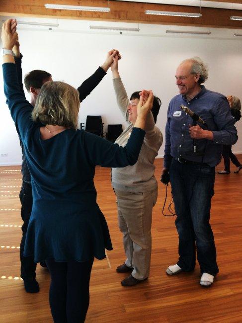 Drei Teilnehmer fassen sich an Händen und heben sie hoch, daneben Siegfried mit Mikrofon