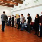 Teilnehmer bilden Reihe und hören den Ausführungen des Coach zu