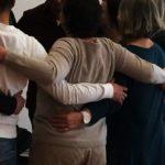 Nahaufnahme, Teilnehmer stehen im Kreis, ihre Arme auf dem Rücken ihrer jeweiligen Nachbarn